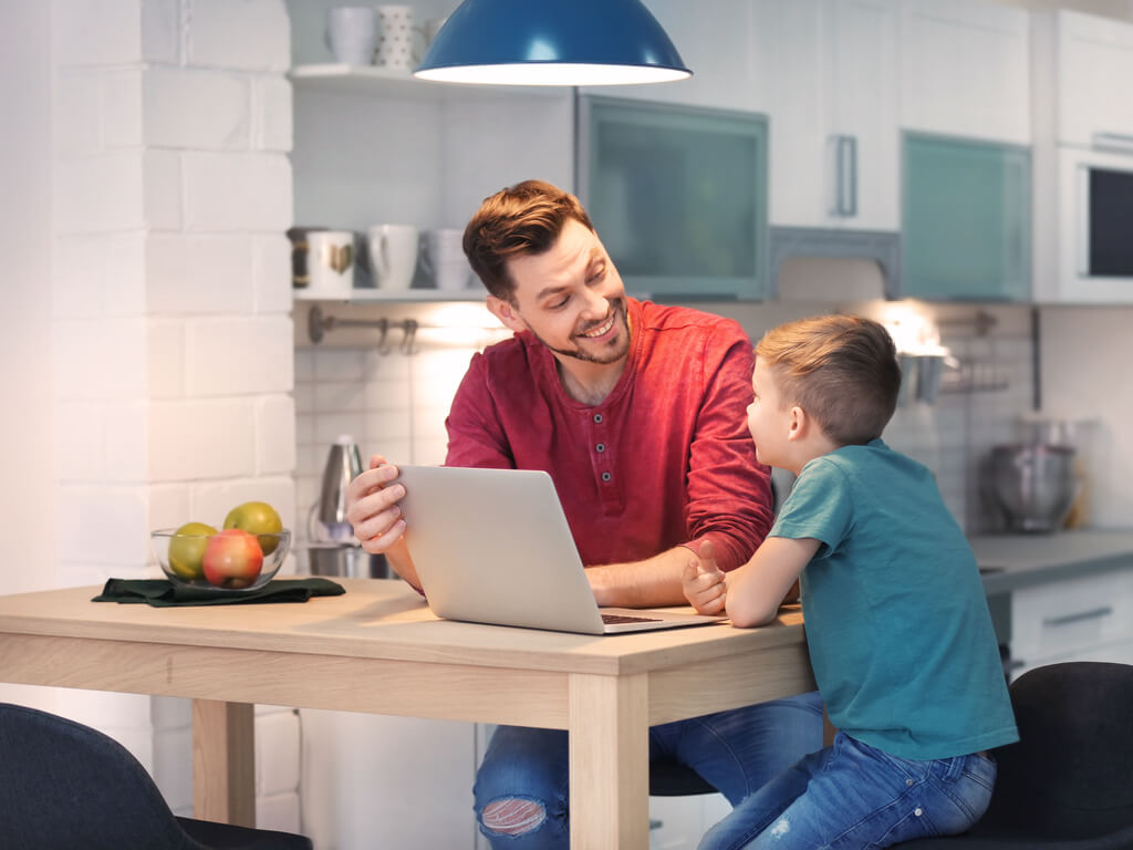 father and son using laptop to discuss kids technology use